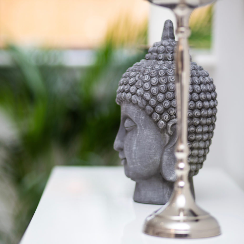 Buddha and silver candle stick