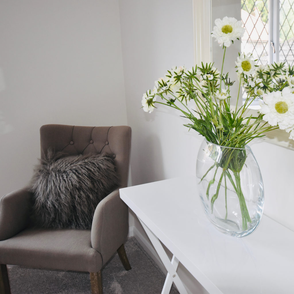 Moon vase and cosmos and grey bedroom chair