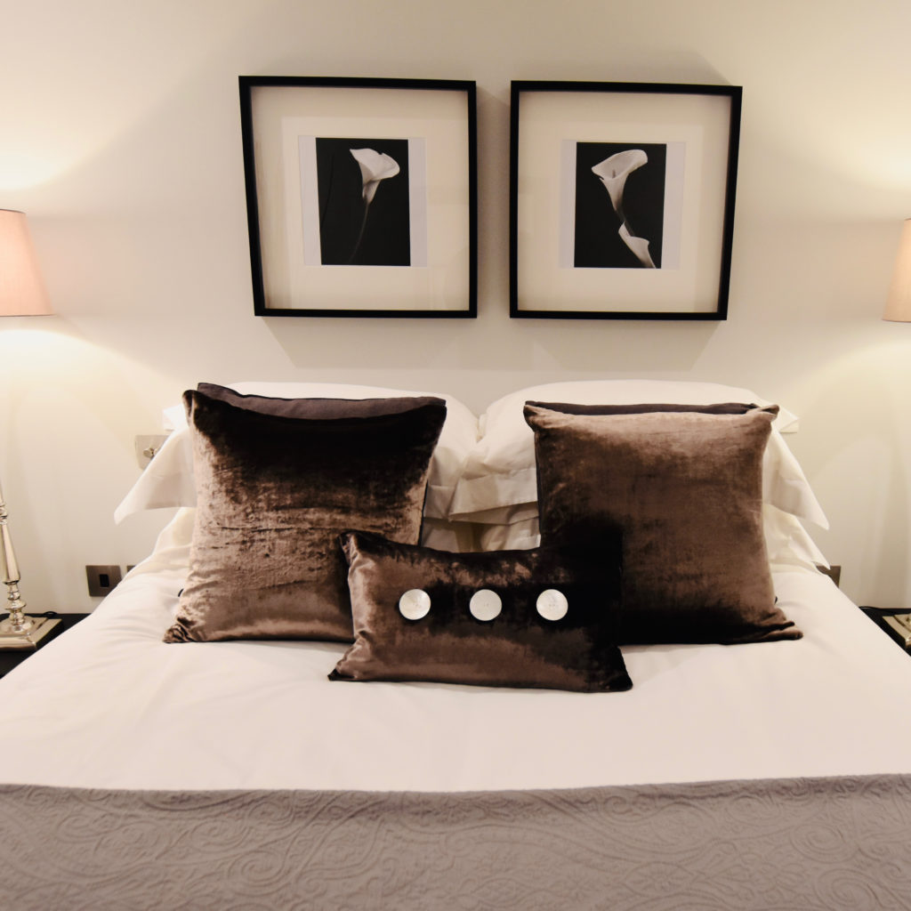 Velvet cushions on bed and lilly prints
