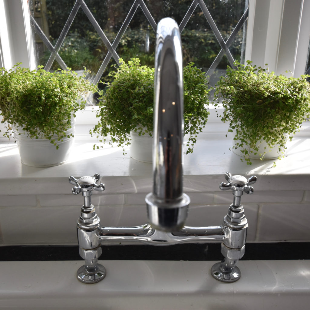 Triple herb pots behind tap